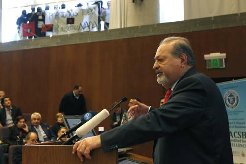 Carlos Slim y al fondo: manta de simpatizantes zapatistas protestando contra él.